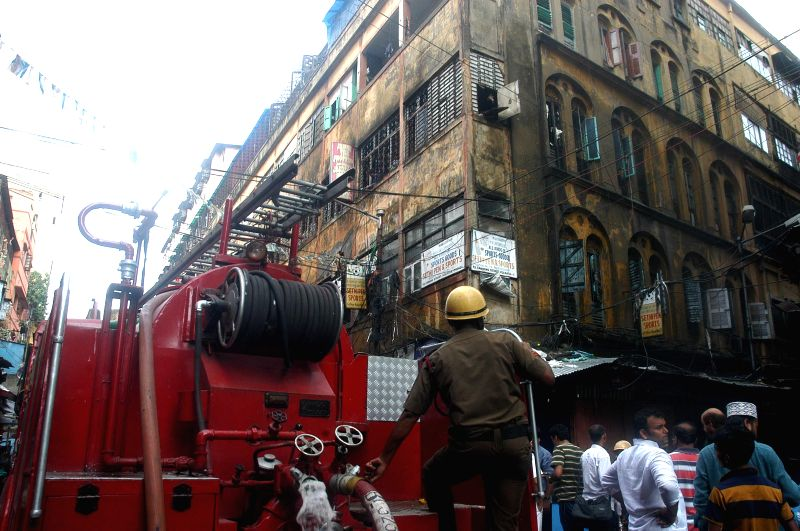 Firefighters fighting to control a fire at Canning Street in Kolkata on August 2, 2014.