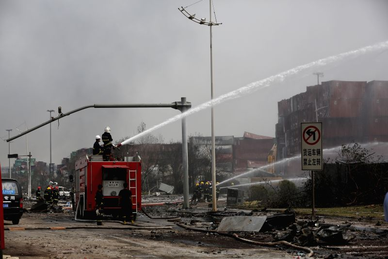 Firefighters put out flames in a container at the site of the explosion in Tianjin, north China, Aug. 14, 2015. An explosion, which occurred Wednesday night at a ...
