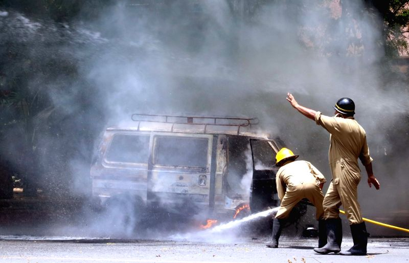 Firefighters try hard to douse a fire that broke out in a car near Parliament police station in New Delhi on May 14, 2016.