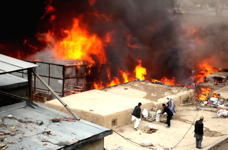 Firefighters try to extinguish a fire at a market in Kabul, Afghanistan, Dec. 5, 2015. Several shops turned to ashes as a massive fire engulfed a market in a main ...