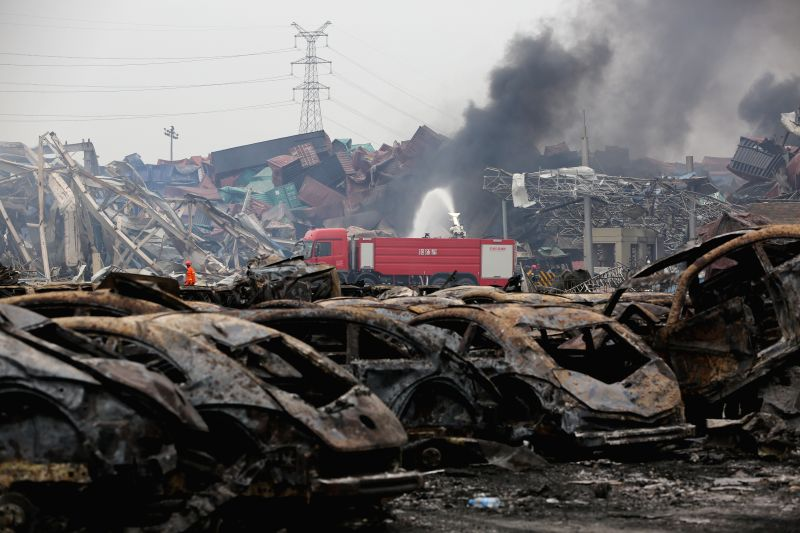 Firefighters work at the warehouse explosion site in Tianjin, north China, Aug. 14, 2015. The death toll has risen to 56, including 21 firemen, from massive ...