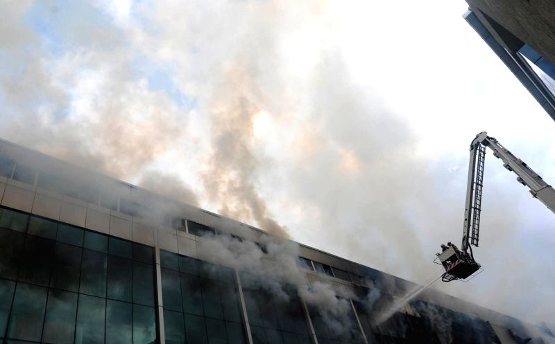 Firemen try hard to douse a fire that broke out at AMR Tech Park and engulfed all the four floors of the building in Bangalore on July 18, 2014.