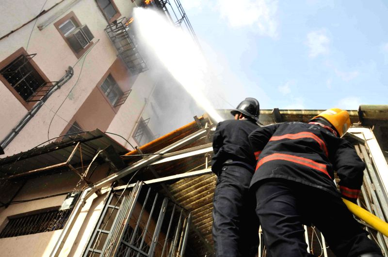 Firemen try to douse a fire breaks that broke out at the fifth floor of the Central Railway administrative building next to the CST Railway Station in Mumbai on June 27, 2014. At least eight fire ...