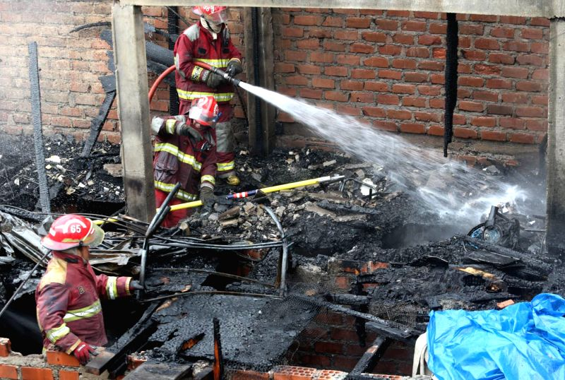 Firemen work at the scene of a fire in Lima, Peru, on Nov. 27, 2015. According to local press, a girl died in the fire that began in a recycling workshop, and spreaded ...