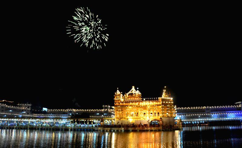 Fireworks light-up the night sky above the Golden Temple on Parkash Utsav of Sri Guru Granth Sahib (410th anniversary of installation of the Guru Granth Sahib) in Amritsar on Sept 1, 2014.