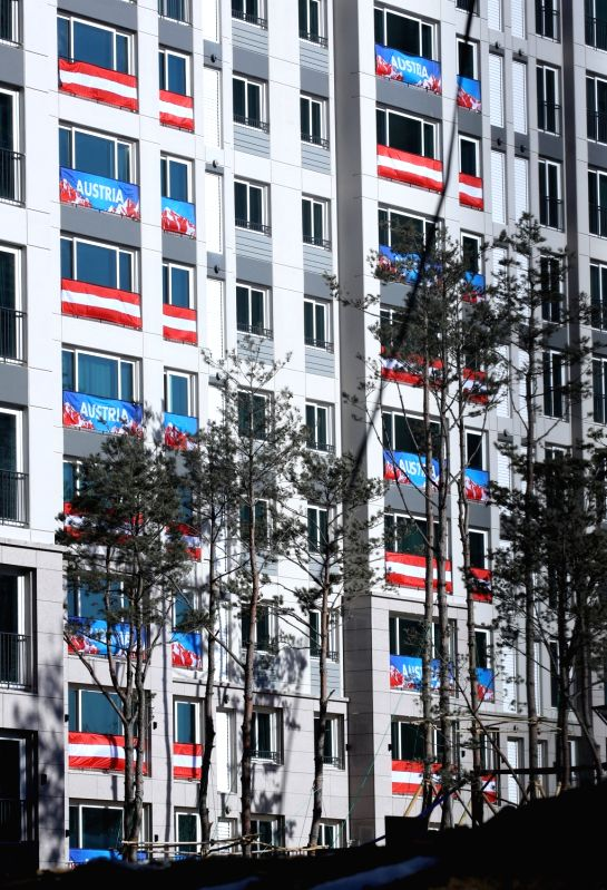 Flags of Austria hang in the windows of apartments at an athletes' village in the alpine city of PyeongChang, the venue for the 2018 Winter Olympics, on Jan. 30, 2018. An Austrian ...