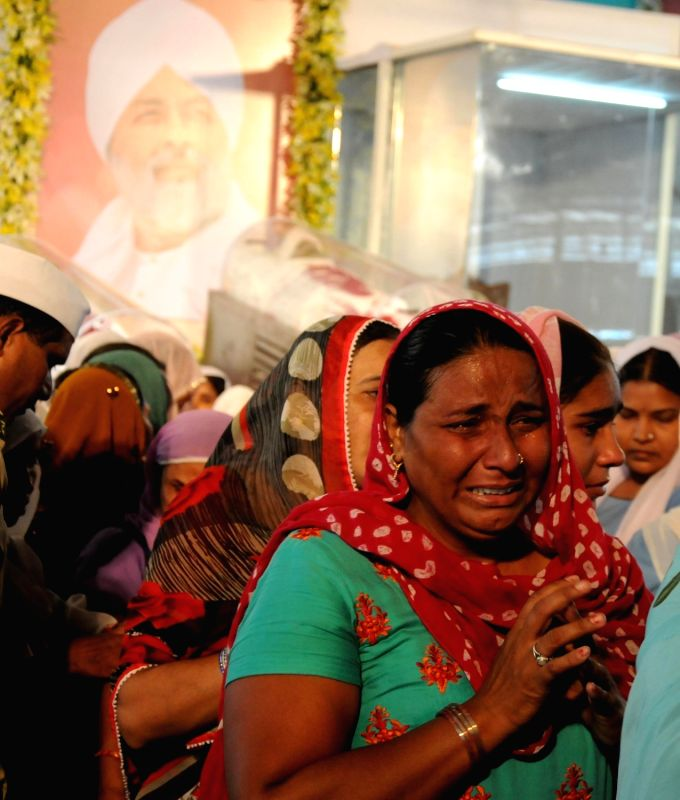 Follower of Sant Nirankari Mission head Baba Hardev Singh who was killed in a road accident in Canada mourn his death in New Delhi, on May 17, 2016. - Hardev Singh