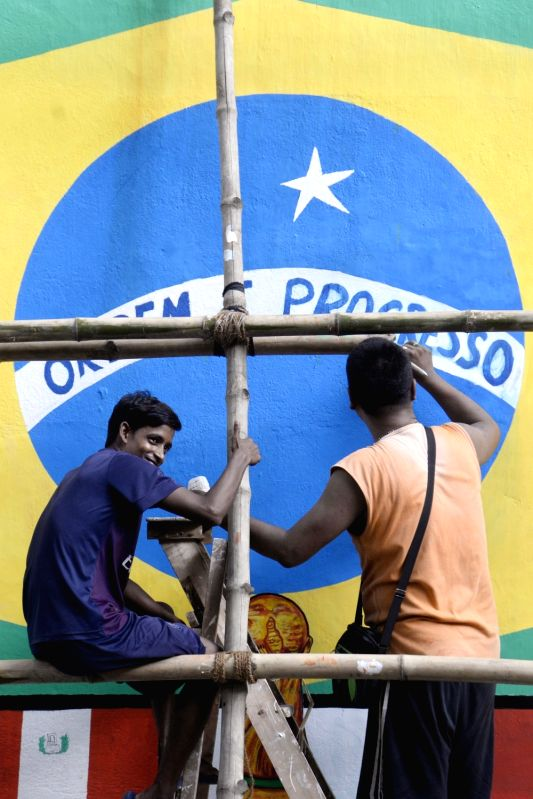 Football fans paint a wall on the theme of FIFA World Cup 2018, in Kolkata on June 12, 2018.