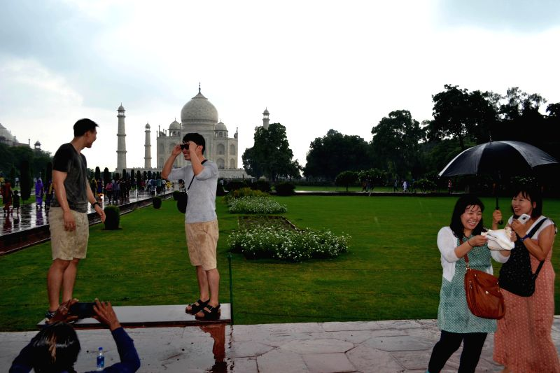 Foreign tourists enjoy themselves at Taj Mahal in Agra on Aug 11, 2014.