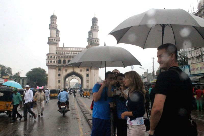 Foreign tourists enjoy themselves during rains at Charminar in Hyderabad on Aug 29, 2014.