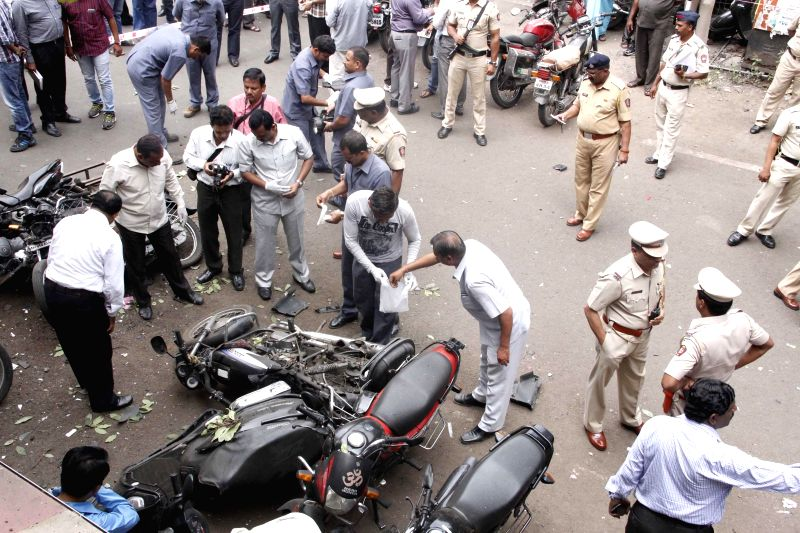 Forensic experts collect evidence from the parking lot where an explosive device fixed to a motorcycle blew-up in Pune on July 10, 2014. Three people, including a police constable and a woman, were ..