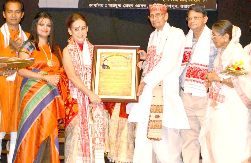 Former Asom Sahitya Sabha President and senior journalist Kanak Sen Deka felicitates Sattriya dancer Indira P P Bora (2nd lft) for her contribution in the field of Sattriya dance during a programme ..