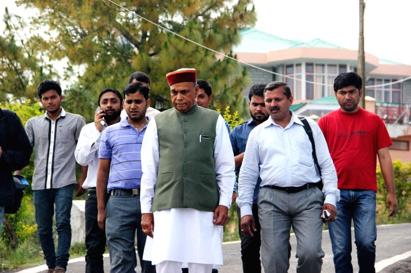 Former Himachal Pradesh Chief Minister and BJP leader Prem Kumar Dhumal arrives to cast his vote at a polling booth in Hamirpur of Himachal Pradesh on May 7, 2014.