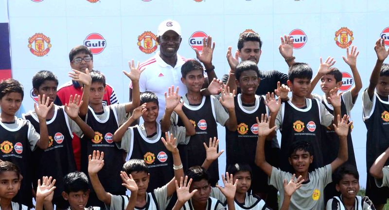 Former Manchester United player Dwight Yorke playing football with budding players at a football clinic in Kolkata on July 27, 2016.