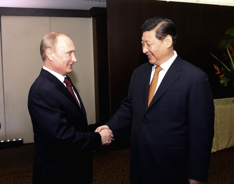Chinese President Xi Jinping (R) meets with Russian President Vladimir Putin in Fortaleza, Brazil, July 14, 2014.