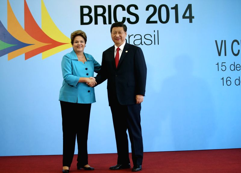 Chinese President Xi Jinping (R) shakes hands with Brazilian President Dilma Rousseff during the sixth BRICS summit in Fortaleza, Brazil, July 15, 2014. ...