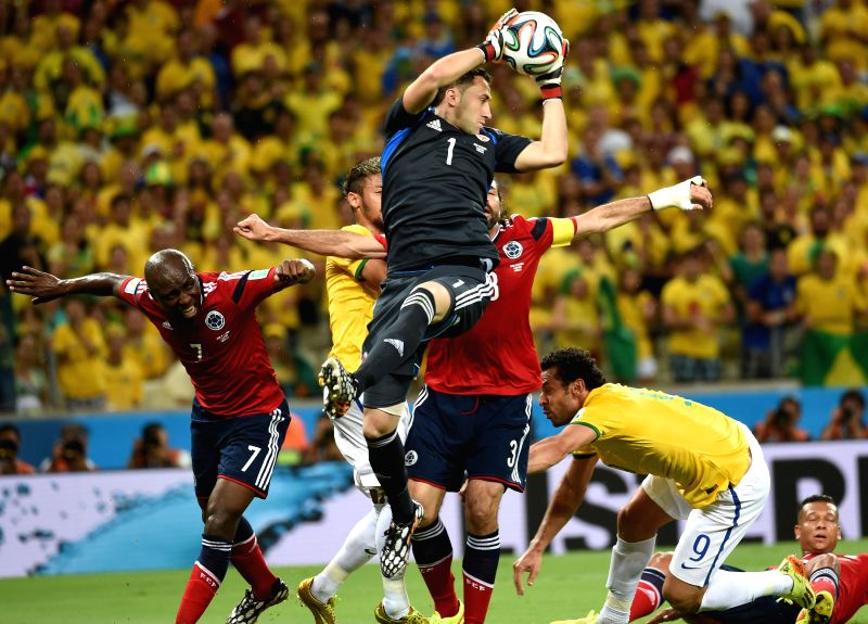 Colombia's goalkeeper David Ospina (front) grabs the ball during a quarter-finals match between Brazil and Colombia of 2014 FIFA World Cup at the Estadio Castelao .