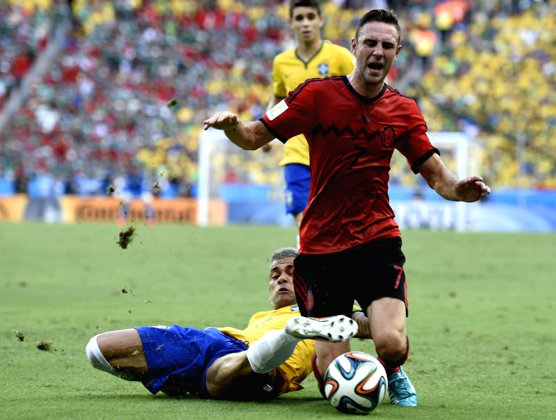 Brazil's Dani Alves (bottom) vies with Mexico's Miguel Layun during a Group A match between Brazil and Mexico of 2014 FIFA World Cup at the Estadio Castelao ...