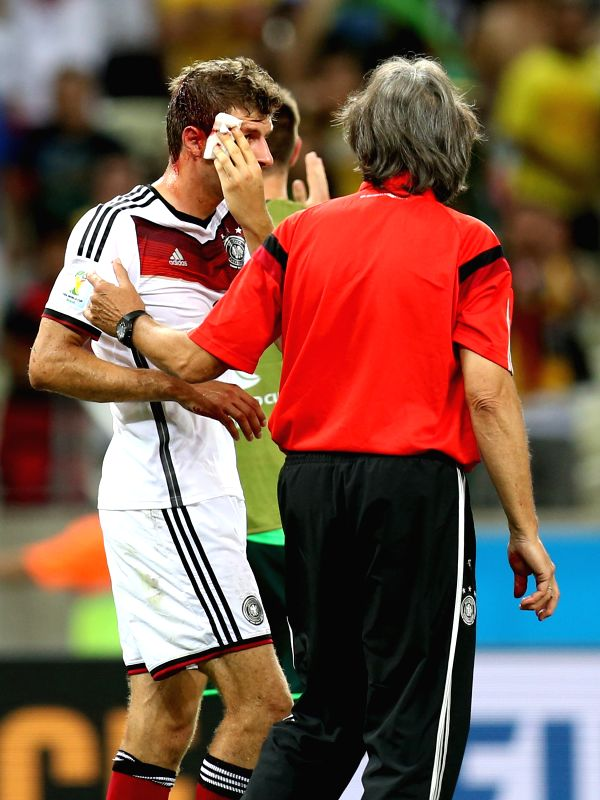 Thomas Muller (L) of Germany bleeds at the end of a Group G match between Germany and Ghana of 2014 FIFA World Cup at the Estadio Castelao Stadium in Fortaleza, ..