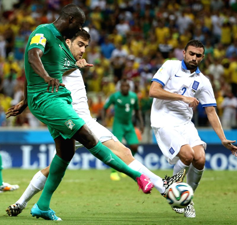 (Cote d'Ivoire's Yaya Toure (1st L) competes with Greece's Sokratis Papastathopoulos during a Group C match between Greece and Cote d'Ivoire of 2014 FIFA World ...