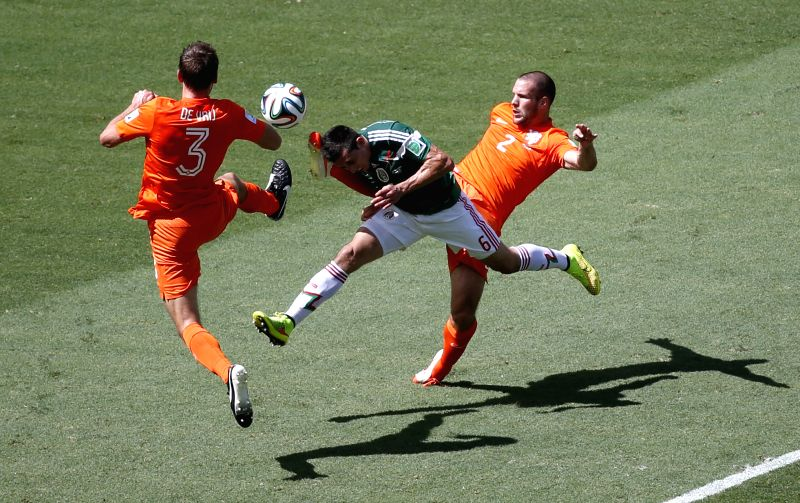 Mexico's Hector Herrera (C) vies with Netherlands' Stefan de Vrij (L) and Ron Vlaar during a Round of 16 match between Netherlands and Mexico of 2014 FIFA World ..