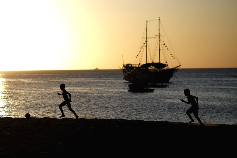 Two boys play football on a beach in Fortaleza, Brazil, June 29, 2014.