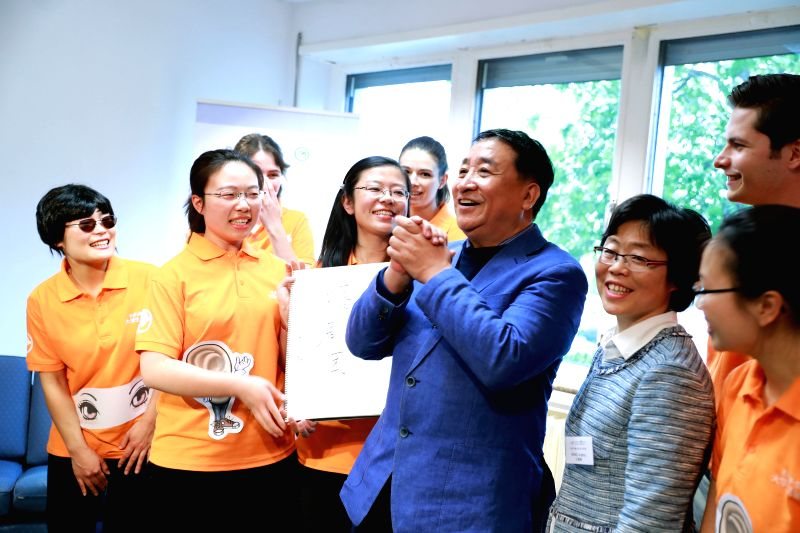 FRANKFURT, April 29, 2017 - Chinese cross talk artist Jiang Kun (4th R) interacts with his fans at Frankfurt Confucious Institute during his visit to Germany on April 28, 2017. - Jiang Kun