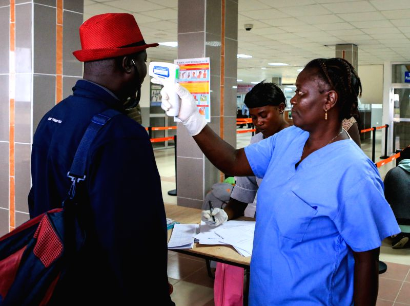 An airport worker measures body temperature for passengers at the Lungi International Airport in Freetown, capital of Sierra Leone, Aug. 14, 2014. The death toll ..