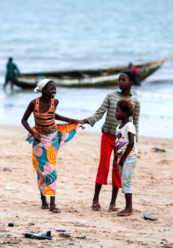 Three girls play on the beach nearby a ferry port linking the Lungi International Airport and the downtown of Freetown, capital of Sierra Leone, on Aug. 14, 2014. .