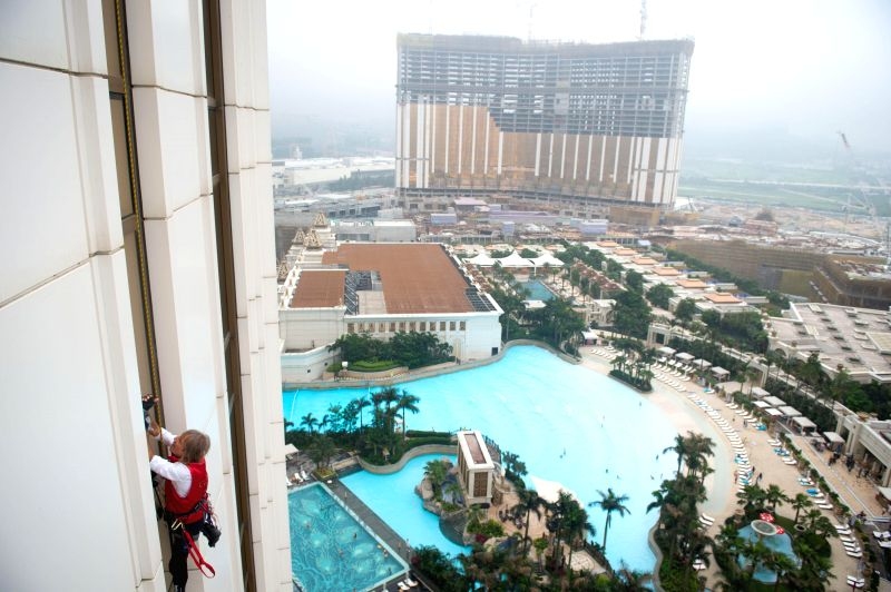 "French ""Spiderman"" Alain Robert climbs Galaxy Macau hotel using safety harness in Macau of China on April 23, 2014."