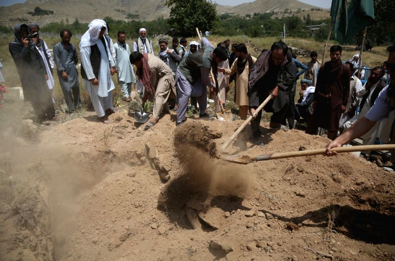 : Friends and relatives throw earth on the tomb of a suicide attack victim in Kabul, capital of Afghanistan, July 23, 2018. At least 14 people were killed and over ...