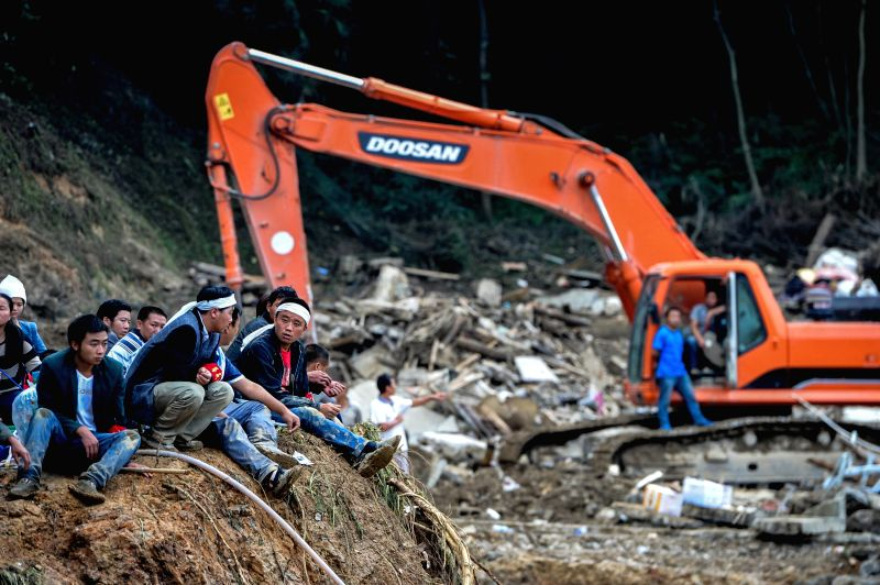 Relatives mourn for victims at the site of landslide in Yingping Village of Fuquan City, southwest China's Guizhou Province, Aug. 29, 2014. The death toll has ...