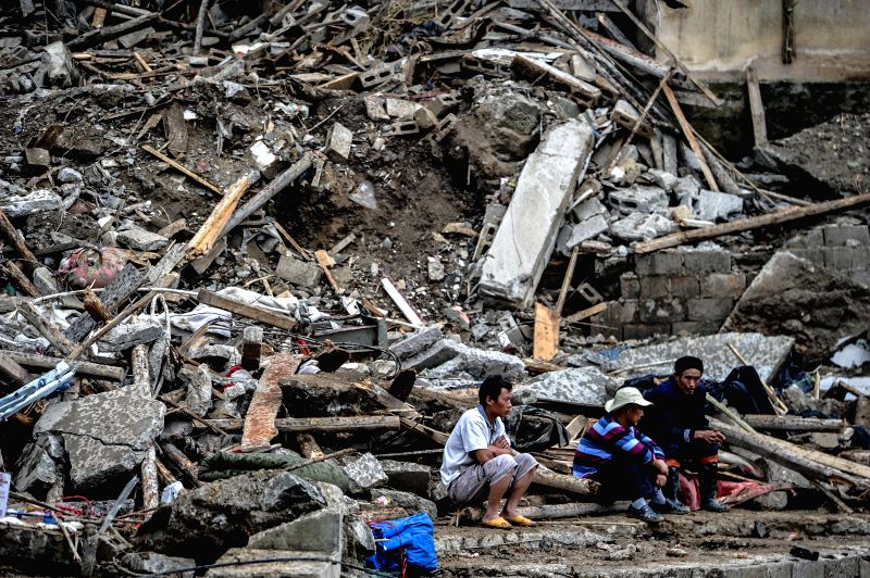 Relatives of victims stand in front of debris of landslide in Yingping Village of Fuquan City, southwest China's Guizhou Province, Aug. 29, 2014. The death toll has .