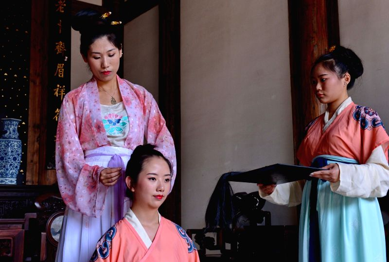 A girl (front) performs a hair-pinning ceremony, the Chinese traditional coming-of-age ritual for girls, in Fuzhou, capital of southeast China's Fujian Province, May ...