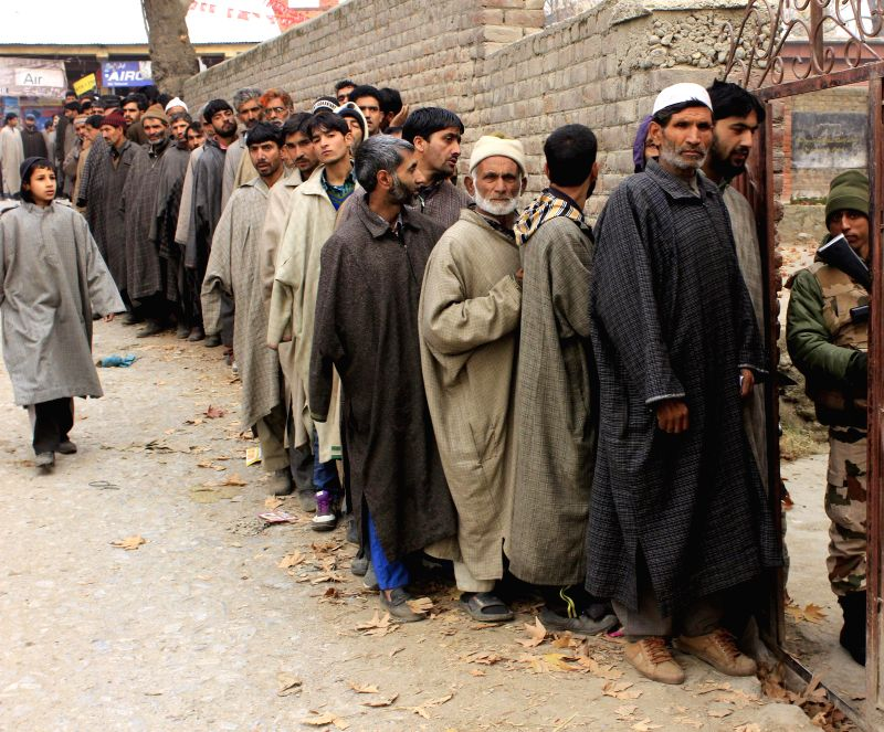 People queue-up outside a  polling booth to cast their votes during the first phase of Jammu and Kashmir polls in Ganderbal district of the state on Nov 25, 2014.