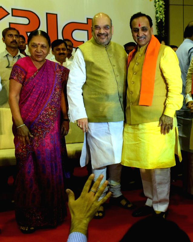 Gandhinagar : Newly elected Gujarat Chief Minister Vijay Rupani with BJP chief Amit Shah and former Gujarat Chief Minister Anandiben Patel during a swearing-in ceremony in Gandhinagar on Aug 7, 2016. - Vijay Rupani, Amit Shah and Anandiben Patel
