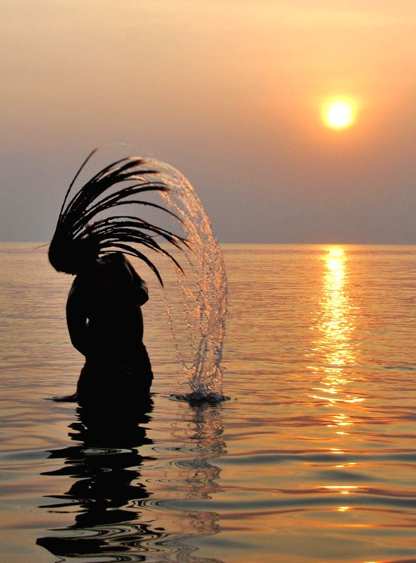 An ascetic takes a holy dip at the Gangasagar island, a day ahead of `Makar Sankranti`,  some 160 km south of Kolkata on Jan 13, 2015.