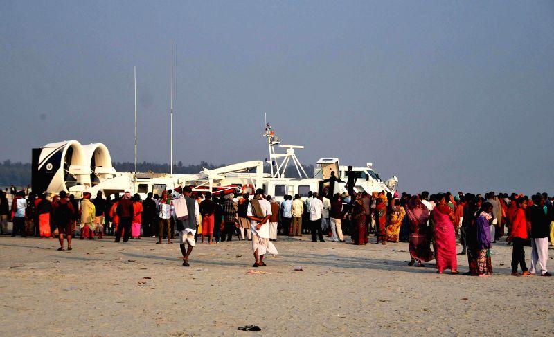 Pilgrims gather near a Hovercraft at the Gangasagar island some 160 km south of Kolkata on Jan 13, 2015.