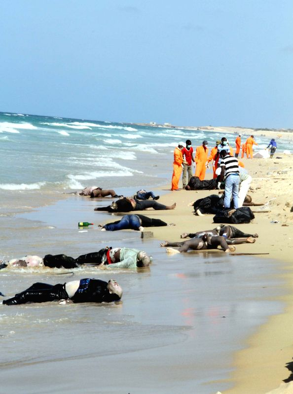 GARABULLI, Aug. 25 Rescue workers transfer bodies on the seashore in Garabulli, Libya, on Aug. 25, 2014. Libya's coast guard confirmed on Saturday that a wooden boat carrying some 170 ...