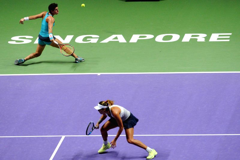 Garbine Muguruza (front) and Carla Suarez Navarro of Spain compete against Martina Hingis of Switzerland and Sania Mirza of India on WTA's women's doubles final ... - Martina Hingis and Sania Mirza