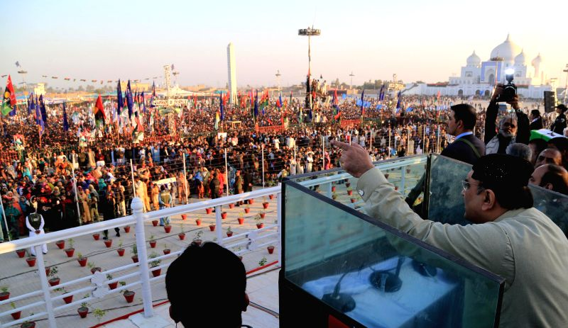 Former Pakistan's President Asif Ali Zardari (R) addresses his supporters outside the Bhutto family mausoleum, commemorating the seventh anniversary of ..