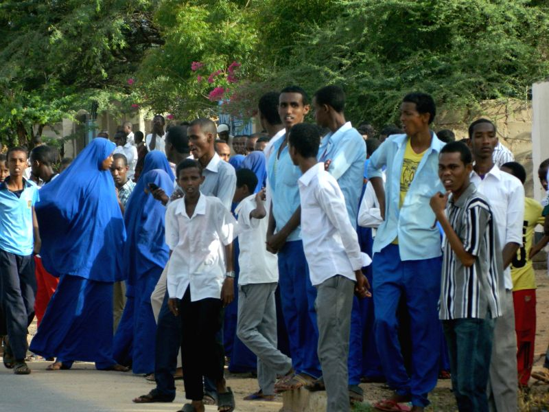 Residents watch at a distance from the university campus in Garissa, Kenya, April 2, 2015. At least 15 people have been confirmed dead and 65 others injured after ...
