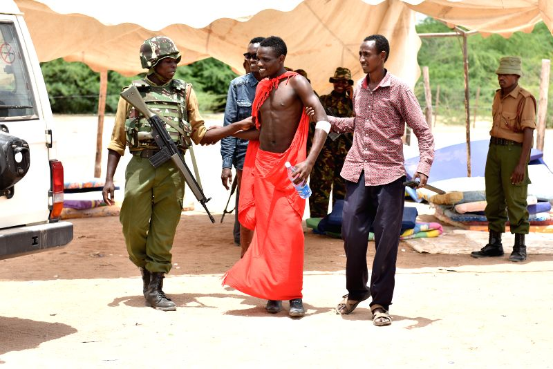 A survivor student (C) with the help of a soldier and his friend prepares leave for home in Garissa, Kenya, April 4, 2015. A total of 663 survivors from a Kenyan ...