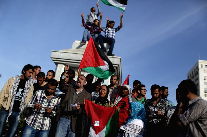Palestinians wave Palestinian flags as they gather to celebrate a newly made reconciliation deal between the Palestine Liberation Organization (PLO) and the Hamas to .
