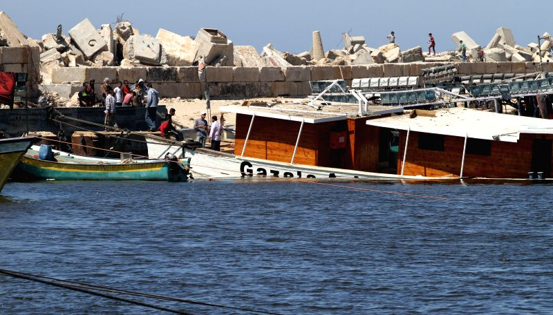 Palestinians inspect the Gaza's Ark, a Palestinian-built protest boat which was preparing to run Israel's naval blockade, after it was damaged in an explosion at the .