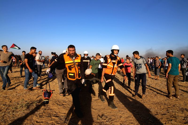 GAZA, Aug. 10, 2018 - Palestinian medics carry a wounded man during clashes with Israeli troops on the Gaza-Israel border, east of the southern Gaza Strip City of Khan Younis, on Aug. 10, 2018. Two ...