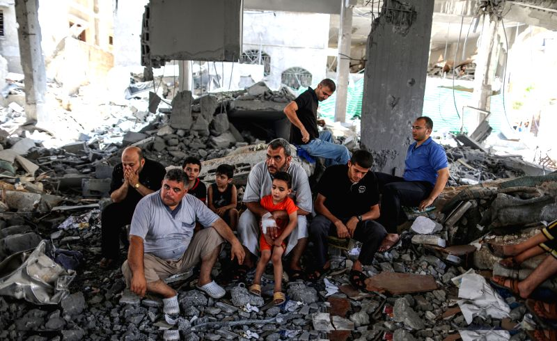 Palestinian men pray on the rubble during Friday prayers at Al-Sousi mosque that was destroyed by Israeli military forces during the latest fighting between Israel and