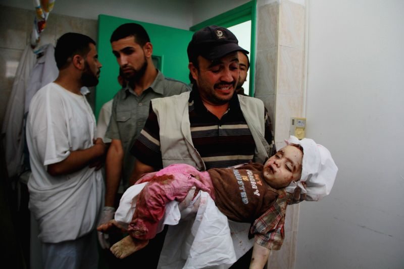 A relative shows the body of Razaq Abu Taha, a one-year-old Palestinian baby who medics said was killed in an Israeli airstrike on their house, at a hospital in the ...