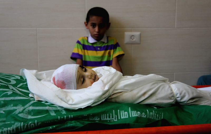 A Palestinian boy stands next to the bodies of Ali Mohammed Dief and his mother during the funeral in the northern Gaza Strip town of Jabaliya on Aug. 20, 2014. Ali, ...