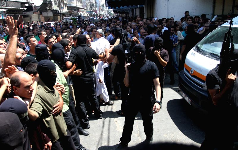 Palestinian citizens and Hamas gunmen gather at the scene of a public execution of Palestinians suspected of collaborating with Israel in a street in downtown Gaza ...